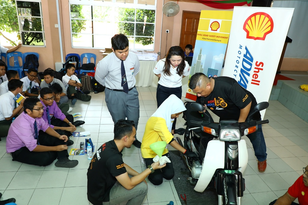 Shell Lubricants Mktg GM May Tan (R) watches as students learn how to ch...